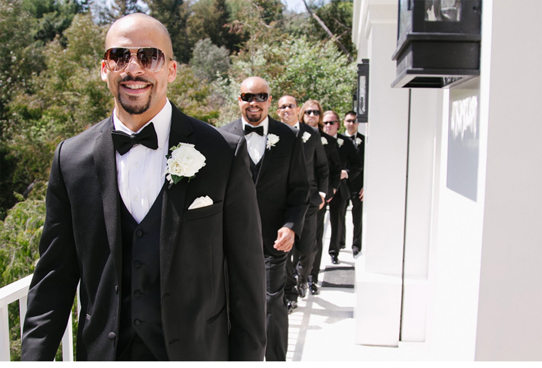 The Men Dress Up in Black Tuxedos, Bow Ties and White Floral Boutonnieres