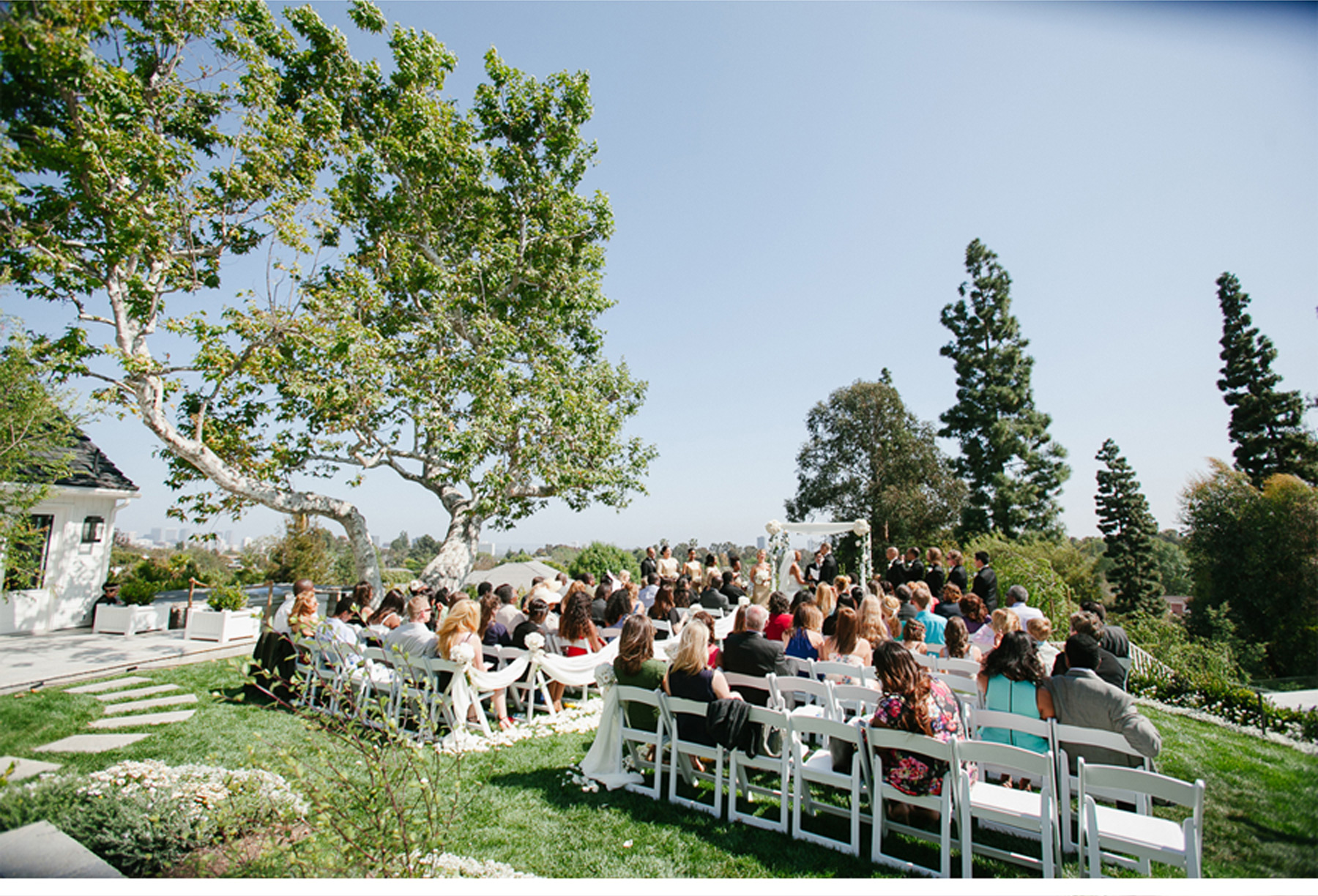 Wedding Guests Enjoy the Outdoor Ceremony on White Chairs