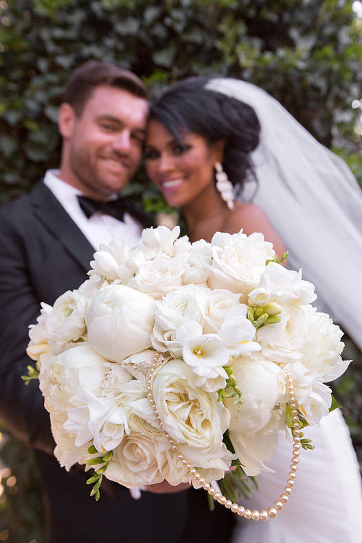 The Bride and Groom Pose with a White Bouquet with Pearls