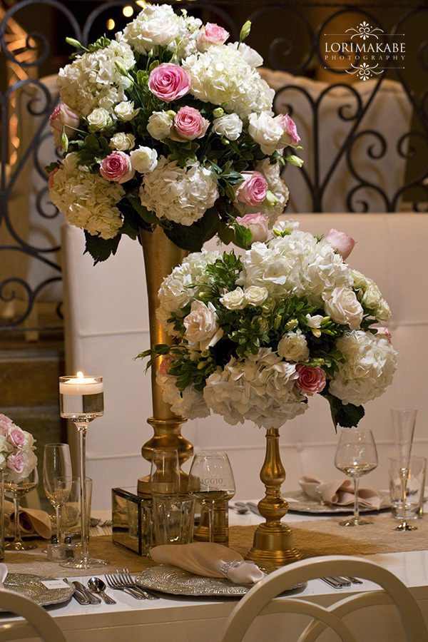 Tall Vases Hold White and Pink Flowers on Each Table