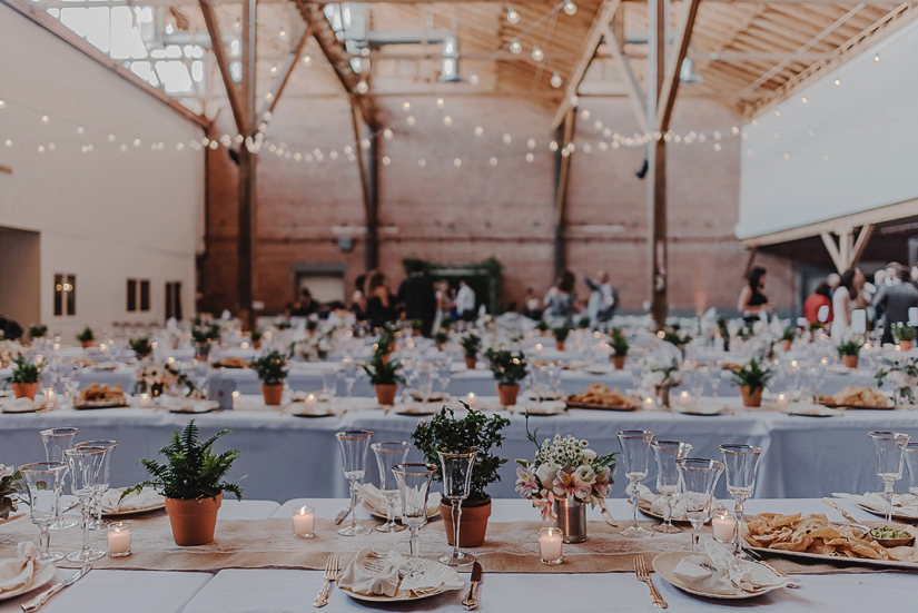 Rustic Table Settings Complement the Venue's Swag Lighting and Exposed Brick