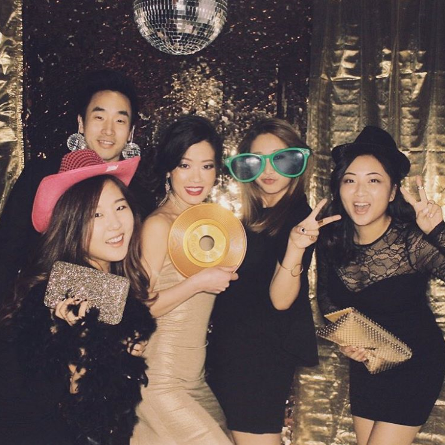 Party Goers Pose With Groovy Props and Disco Ball